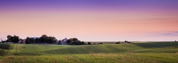 Malowniczy krajobraz podczas zachodu słońca. wielobarwne niebo. grunty rolne na tle wieczornego nieba. krajobraz letniego wieczoru to symbol ciszy i spokoju