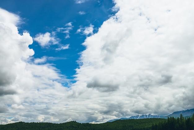 Malowniczy krajobraz przyrody z pięknymi chmurami w błękitne niebo. kolorowy cloudscape z chmurami nad ośnieżonymi górami i lasem. tle przyrody niebo z białymi chmurami. naturalne pochmurne niebo tło.