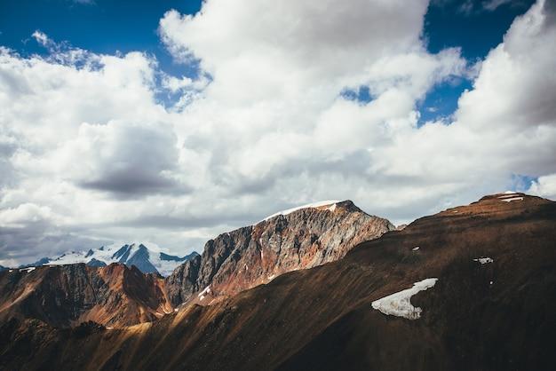 Malowniczy krajobraz wyżyny z wielkim ośnieżonym szczytem górskim za kolorową brązową czerwoną pomarańczową ścianą górską w słońcu. słoneczna sceneria gór z wysoką, jaskrawobrązowo-czerwono-pomarańczową górą i dużym śnieżnym szczytem