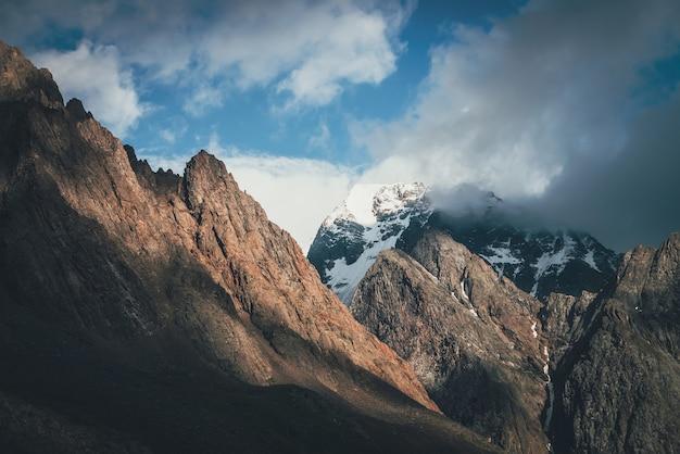 Malowniczy krajobraz z wielkimi skałami i ośnieżonymi górami w słońcu w niskich chmurach. wspaniały widok na szczyt góry ze śniegiem w słońcu w pochmurne niebo. niesamowita sceneria ze śnieżnobiałym szczytem rozświetlonym słońcem.