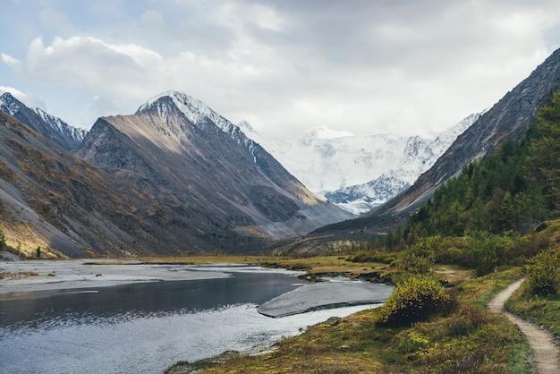 Malowniczy krajobraz ze ścieżką wzdłuż strumieni wodnych w górskiej dolinie w jesiennych kolorach z widokiem na ośnieżone góry. kolorowa jesienna sceneria ze ścieżką w pobliżu górskiego potoku i pokrytych śniegiem gór