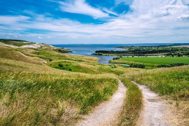 Malowniczy krajobraz ze wzgórzami i polami kwiatowymi oraz błękitnym niebem