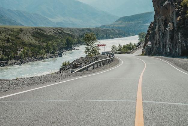 Malowniczy krajobraz ze znakiem drogowym ograniczenia prędkości na górskiej autostradzie. piękny widok na szlak w górach. krajobraz z drogą asfaltową z oznakowaniem drogowym. autostrada z ciągłą linią i górską rzeką.