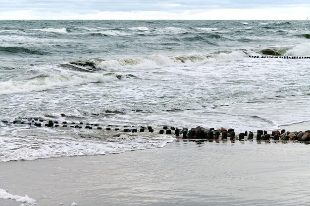 Malowniczy widok na błękitne morze z bulgoczącymi i pieniącymi się falami. vintage długie drewniane falochrony rozciągające się daleko do morza, zimowy krajobraz morza bałtyckiego. cisza, samotność, spokój i spokój.