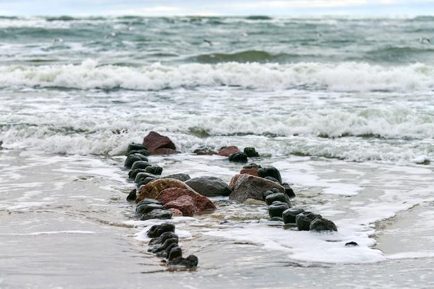 Malowniczy widok na błękitne morze z pieniącymi się falami. vintage długie drewniane falochrony rozciągające się daleko do morza, zimowy krajobraz morza bałtyckiego. cisza, samotność, spokój i spokój.