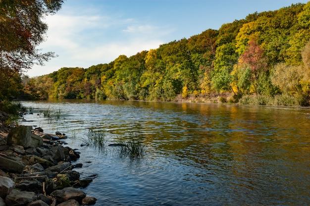 Malowniczy widok na jezioro otoczone drzewami liściastymi w słoneczny ciepły jesienny dzień na tle błękitnego nieba.