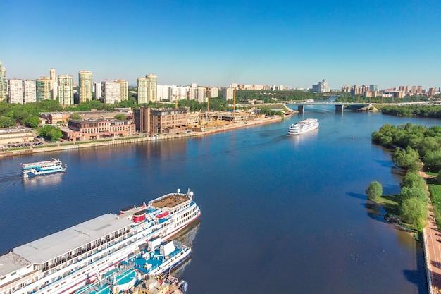 Malowniczy widok na miasto nad rzeką z pływającymi po niej statkami