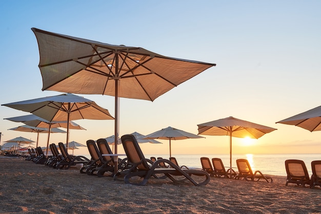 Malowniczy widok na piaszczystą plażę z leżakami na morze i góry o zachodzie słońca. amara dols vita luxury hotel. ośrodek wczasowy. tekirova kemer. indyk.