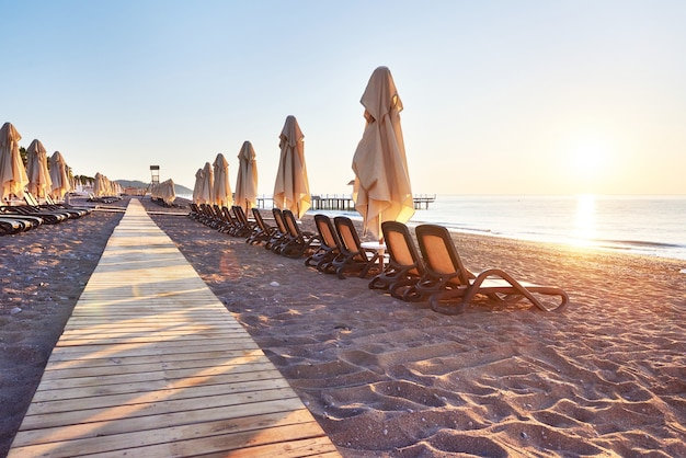 Malowniczy widok na prywatną piaszczystą plażę z leżakami i parasokamy na morze i góry. ośrodek wczasowy.