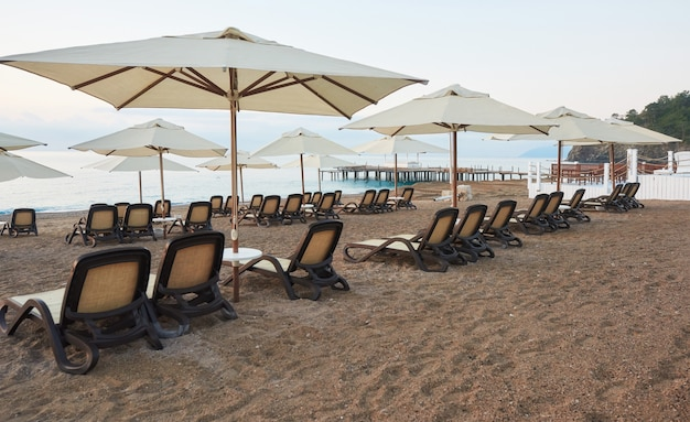 Malowniczy widok na prywatną piaszczystą plażę z leżakami od strony morza i gór. amara dols vita luxury hotel. ośrodek wczasowy. tekirova kemer. indyk.