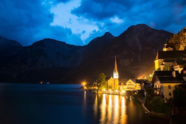 Malowniczy widok na słynne miasto nad jeziorem hallstatt, odbijające się w jeziorze hallstattersee w austriackich alpach
