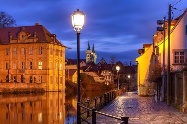 Malowniczy widok na stare miasto i klasztor michelsberg nad rzeką regnitz w nocy w bambergu, bawaria, górna frankonia, niemcy