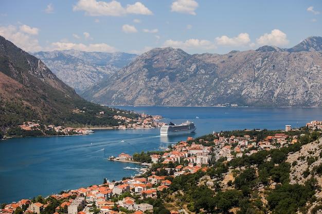 Malowniczy widok na zabytkowe stare miasto w kotorze, zatokę kotorską i statek wycieczkowy odpływający z lovcen mountain, czarnogóra, bałkany