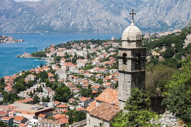 Malowniczy widok na zabytkowe stare miasto w kotorze, zatokę kotorską ze starym kościołem i dzwonnicę na pierwszym planie. lovcen mountain, czarnogóra, bałkany