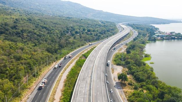 Malowniczy widok z lotu ptaka na dużą autostradę, widok z góry z drona drogi i zielonego lasu w tajlandii