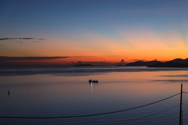 Malowniczy widok z sylwetki łodzi rybackiej na spokojnym oceanie podczas wschodu słońca