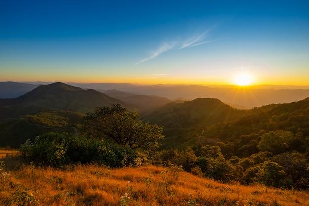 Malowniczy zachód słońca i widok na góry między szlakiem pieszym.