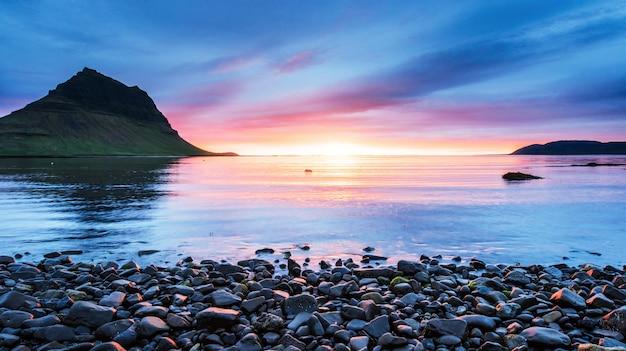 Malowniczy zachód słońca nad krajobrazami i wodospadami. góra kirkjufell, islandia