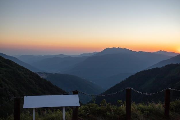 Malowniczy zachód słońca w górach ze światłem słonecznym, pięknym światłem. wieczór letni krajobraz w dolinie z horyzontem, niebem, trawą, kwiatami. pojęcie podróży