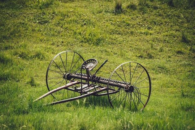 Malowniczy zielony krajobraz ze starym pługiem dla koni ałtajskich z siodłem w polu wśród bujnych traw. minimalistyczne żywe zielone dekoracje z żelaza koń stary pług na tle trawiastego wzgórza z bliska. pług rustykalny.