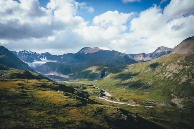 Malowniczy zielony niebieski alpejski krajobraz z górską rzeką w górskiej dolinie w słońcu i dużym lodowcu pod zachmurzonym niebem. cień chmur na zielonej górskiej dolinie. chmury rzucają cień na skały i wzgórza.