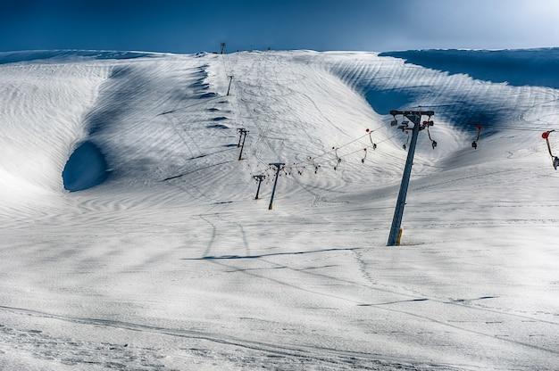 Malowniczy zimowy krajobraz z pokrytymi śniegiem górami, położony w campocatino, turystycznym miasteczku narciarskim w środkowych apeninach we włoszech