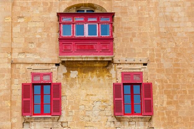 Maltańska architektura, fasada domu z czerwonymi drewnianymi oknami i balkonem na wyspie malta