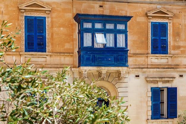 Maltańska architektura, fasada domu z drewnianymi oknami i niebieskim balkonem na wyspie malta