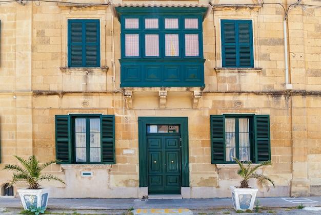 Maltańska architektura, fasada domu z drewnianymi oknami i zielonym balkonem na wyspie malta