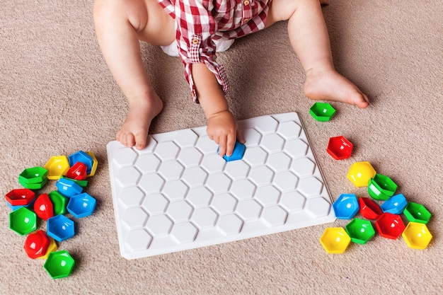 Maluch bawi się plastikową mozaiką na dywanie w pokoju dziecięcym. wczesny rozwój, metoda montessori.