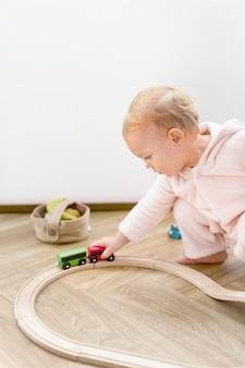 Maluch bawiący się drewnianym pociągiem zabawkowym