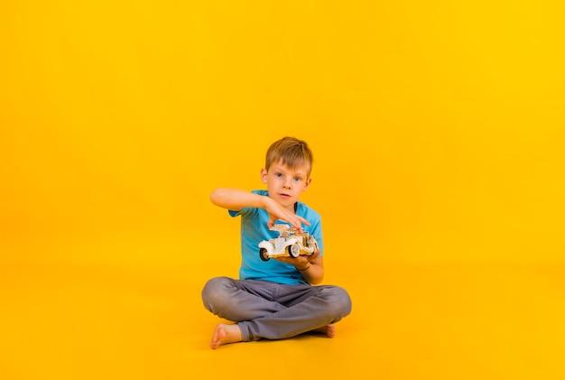 Maluch chłopiec bawi się białym samochodem retro i patrzy w kamerę na żółtym tle z miejscem na tekst