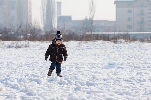 Maluch chłopiec chodzi po pokrytej śniegiem ziemi