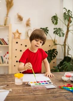Maluch chłopiec w czerwonej koszulce rysuje pędzlem i maluje na białym papierze przy drewnianym stole