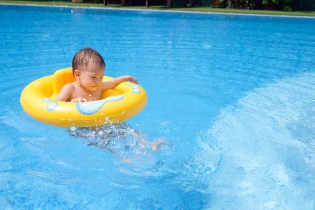 Maluch dobrze się bawi grając z dmuchanym pierścieniem pływackim w basenie