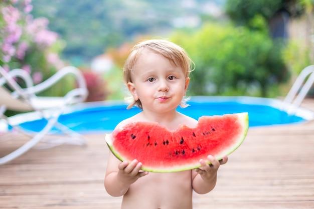 Maluch dziecko jedzenie arbuza w pobliżu basenu podczas letnich wakacji. dzieci jedzą owoce na świeżym powietrzu.