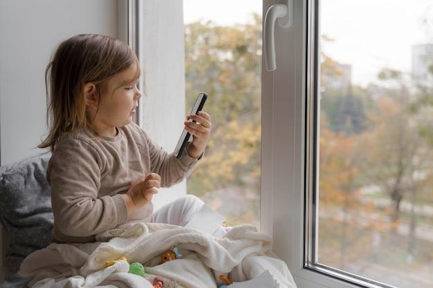 Maluch dziecko przy użyciu telefonu w domu