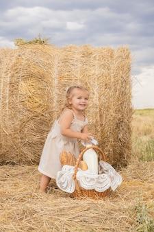 Maluch dziewczyna blond bierze butelkę mleka z koszyka chleba