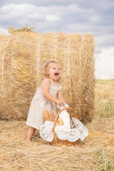 Maluch dziewczyna blond w lnianej sukience bierze butelkę mleka z koszyka chleba