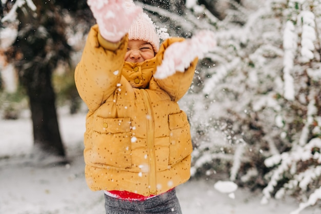Maluch dziewczyna szczęśliwy ze śniegiem w zimie. grając na zewnątrz w święta bożego narodzenia