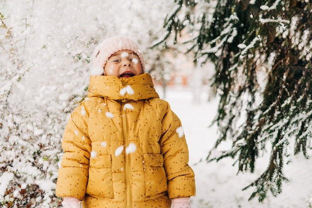 Maluch dziewczyna szczęśliwy ze śniegiem w zimie.