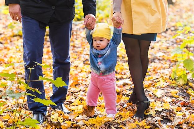 Maluch dziewczyna trzymając się za ręce z matką i ojcem na zewnątrz w dzień jesieni