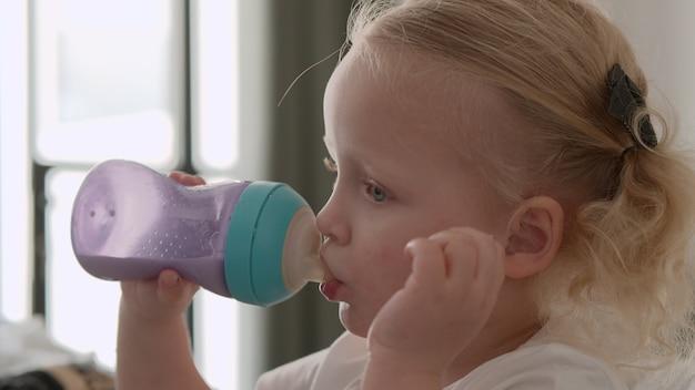 Maluch dziewczynka pije mleko z butelki