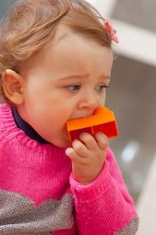 Maluch dziewczynka wkłada do ust gumowe klocki.