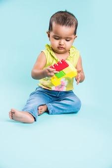 Maluch indyjski lub azjatycki, niemowlę lub dziecko bawiące się zabawkami lub klockami, leżąc lub siedząc na białym tle na jasnym lub kolorowym tle