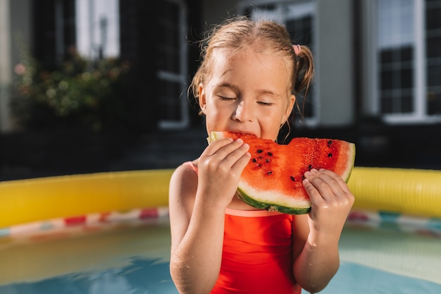 Maluch je arbuza w basenie na podwórku z zamkniętymi oczami. dzieci jedzą owoce na świeżym powietrzu.