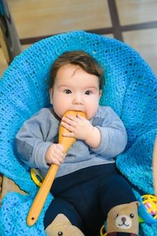 Maluch liże łyżkę. dziecko patrzy na pustą drewnianą łyżkę. gdy zęby są nacinane. swędzenie dziąseł