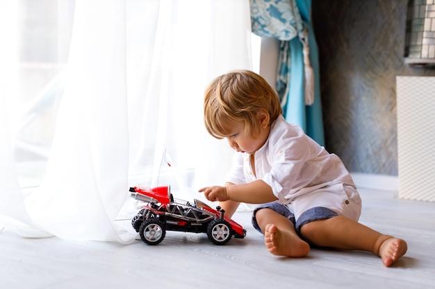 Maluch mały chłopiec siedzi na podłodze domu i bawi się motocyklem-zabawką w domu