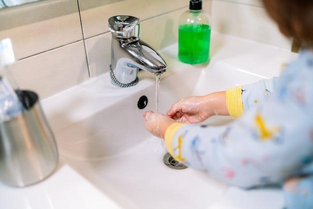 Maluch myje ręce mydłem w celu zapobiegania i ochrony przed koronawirusem covid 19