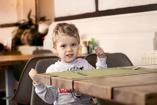 Maluch pokazuje, jaki jest silny. chłopiec siedzi przy stoliku w kawiarni i czeka na swoje zamówienie. pojęcie diety i żywienia dzieci. maluch pokazuje, jaki jest silny. pojęcie diety i żywienia dzieci.